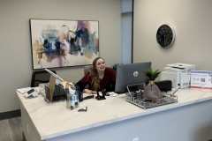 Certified-Medical-Assistant-Veda-Sitting-at-front-reception-desk3